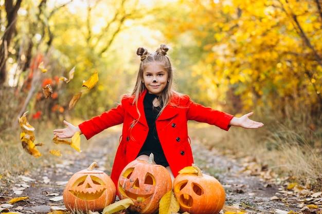 Het leuke meisje kleedde zich in openlucht in halloween-kostuum met pompoenen Gratis Foto