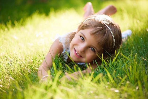 Het leuke meisje ligt op gras in de zomerpark Premium Foto