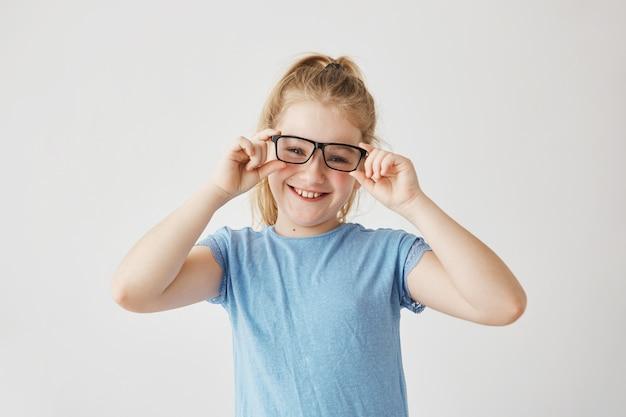 Het leuke meisje met blauwe ogen en lichte haarglimlachen speelt met mamma die haar bril neemt en ze probeert. gelukkige familiemomenten. Gratis Foto