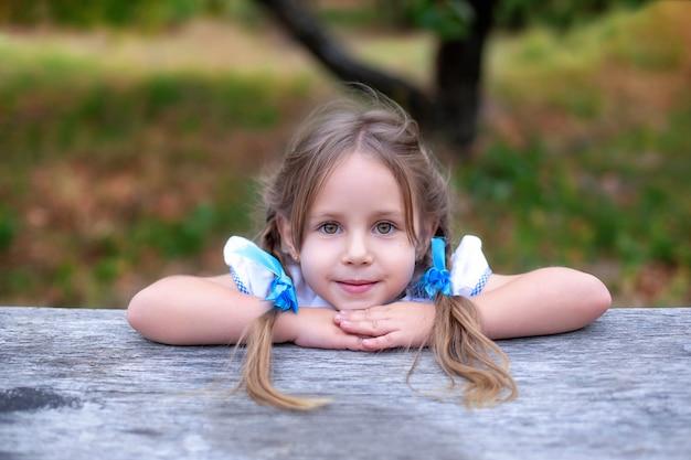 Het leuke meisje met twee vlechten op haar hoofd vouwt handen dichtbij gezicht. glimlachend kindmeisje met grote ogen in de zomertuin. Premium Foto