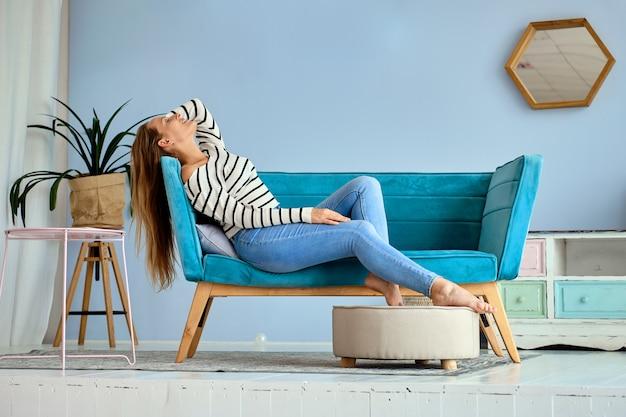 Het leuke meisje ontspant thuis en voelt gelukkig Premium Foto