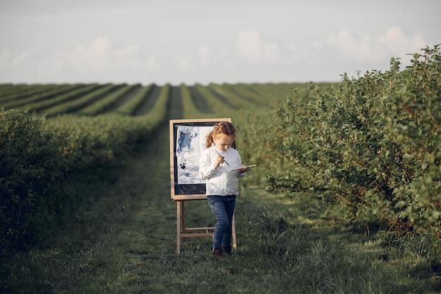 Het leuke meisje schilderen in een park Gratis Foto