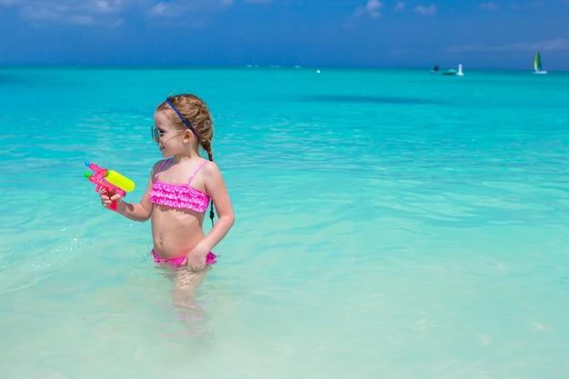 Het leuke meisje spelen met speelgoed tijdens caraïbische vakantie Premium Foto