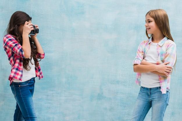 Het leuke meisje stellen voor haar vriend die haar foto met camera vangen tegen blauwe achtergrond Gratis Foto