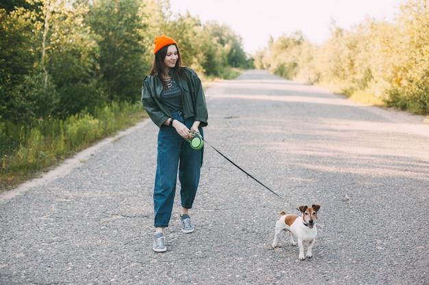 Het leuke moderne tienermeisje in een groen jasje en een oranje hoed loopt met haar hond in aard. Premium Foto