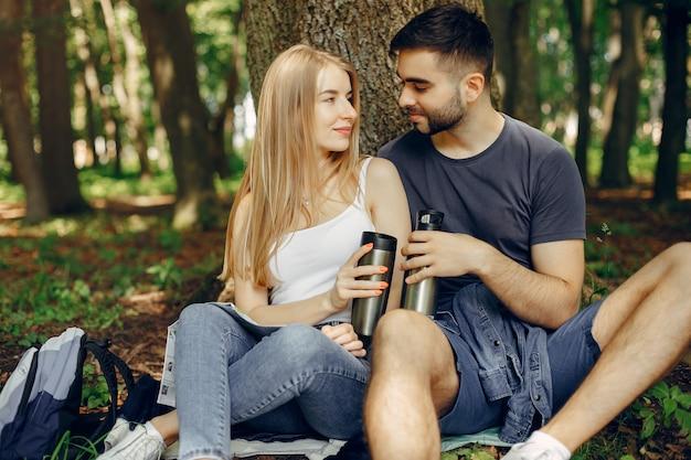 Het leuke paar heeft een rust in een de zomerbos Gratis Foto