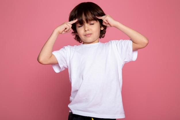 Het leuke schattige portret van de kindjongen in wit t-shirt en zwarte broeken op roze bureau Gratis Foto