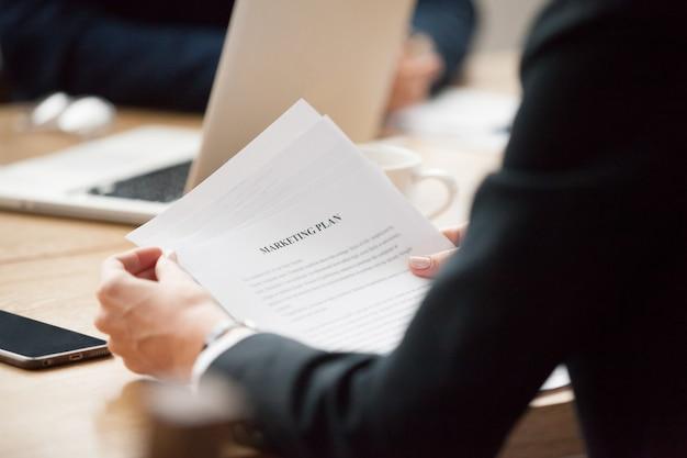 Het lezen van marketingplanconcept, het document van de onderneemsterholding, sluit omhoog mening Gratis Foto