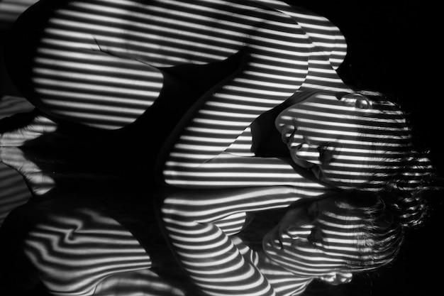 Het lichaam van de vrouw met zwart-wit gestreepte strepen Gratis Foto