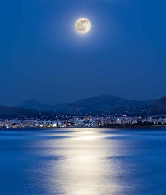Het maanlicht wordt weerspiegeld op de zee in de baai van de stad palermo (italië). Premium Foto