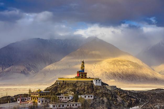 Het maitreya buddha-standbeeld met himalaya-bergen op de achtergrond van diskit-klooster, india. Premium Foto