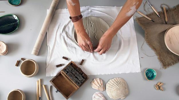 Het maken van een keramisch bord, handgemaakt. het concept van de creatieve persoon. Premium Foto