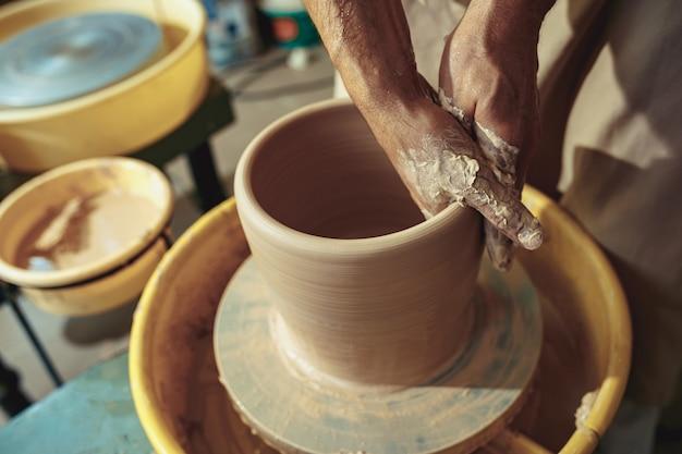 Het maken van een pot of vaas van witte klei close-up. meesterpot. Gratis Foto