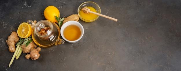 Het maken van gezonde antioxidant en ontstekingsremmende gemberthee met verse gember, citroengras, salie, honing en citroen op donkere achtergrond met kopie ruimte. Premium Foto