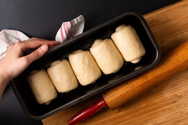 Het maken van het organische eigengemaakte zachte brood van het melkbrood in broodpan op houten raad met exemplaarruimte Premium Foto
