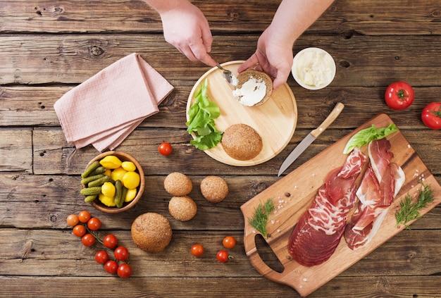 Het maken van sandwiches met vlees en worst op houten tafel Premium Foto