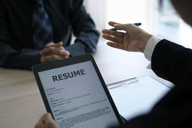 Het management interviewde de aanvragers door de cv uit de e-mail te openen via de smartphone. Premium Foto
