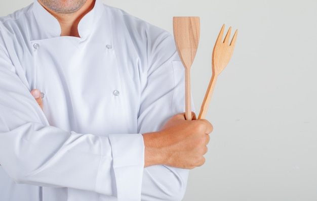 Het mannelijke keukengerei van de chef-kokholding met gekruiste wapens in eenvormig Gratis Foto