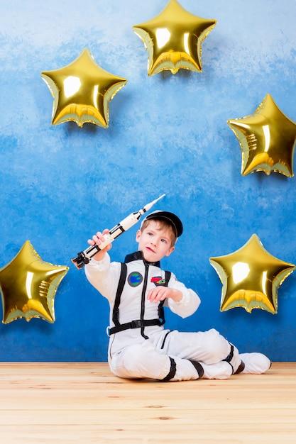 Het mannetje dat van de jong kindjongen in astronaut met raket in wit astronautenkostuum speelt en droomt over het vliegen in kosmos door de sterren die dichtbij de ballons van de gouden ster blijven Premium Foto