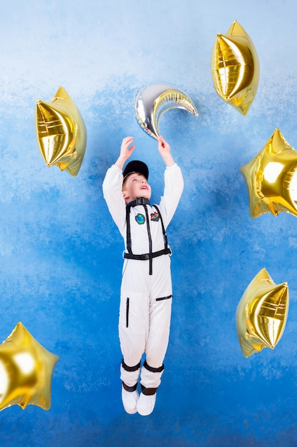 Het mannetje dat van de jong kindjongen in astronaut met zilveren maan in wit astronautenkostuum speelt en droomt over het vliegen in kosmos door de sterren die dichtbij de ballons van de gouden ster blijven Premium Foto