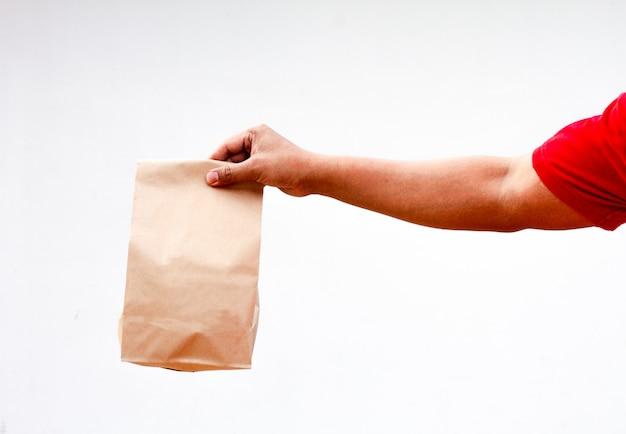 Het mannetje houdt in hand bruine duidelijke lege lege ambachtdocument zak voor meeneem die op witte achtergrond wordt geïsoleerd. verpakkingssjabloon mock up. levering dienstverleningsconcept. kopieer ruimte. advertentieruimte Premium Foto