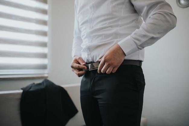 Het mannetje maakt zwarte riem op zijn broek vast Gratis Foto