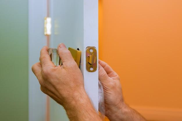 Het manusje van alles herstelt het deurslot in de handen van de arbeider die nieuw deurkast installeren Premium Foto