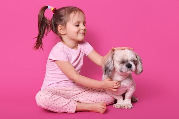 Het meisje aait haar pekingees terwijl het zitten met gekruiste benen op vloer. aanbiddelijk kind houdt van haar huisdier. schattige lachende jongen kijkt naar haar hond, draagt roze shirt en broek, met paardenstaarten. kinderen concept. Gratis Foto
