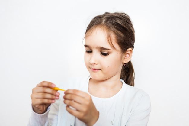Het meisje behandelt haar favoriete speelgoed, gips, dokter spelen, spelletjes in de kindertijd, kinderkamer Premium Foto