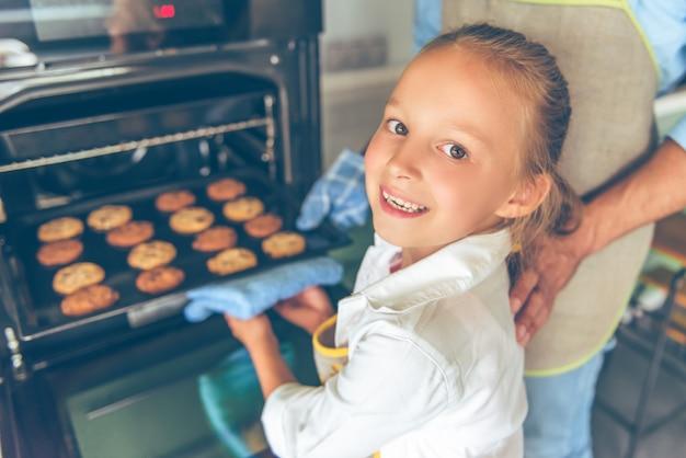 Het meisje bekijkt camera en glimlacht terwijl het maken van koekjes. Premium Foto