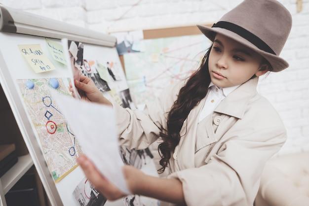 Het meisje bekijkt foto's dichtbij aanwijzingenraad. Premium Foto