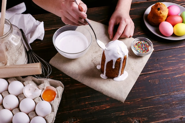 Het meisje bereidt pasen bakken, smeert de cake met ijsvorming en bestrooit met gekleurd poeder. voorbereiding op de vakantie op de keukentafel op donker. Premium Foto
