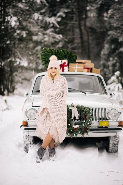 Het meisje bereidt zich voor op kerstmis, is bedekt met een deken op de achtergrond van een retro-auto, waarvan het dak een kerstboom is, geschenken en een krans in het winter besneeuwde bos. Premium Foto
