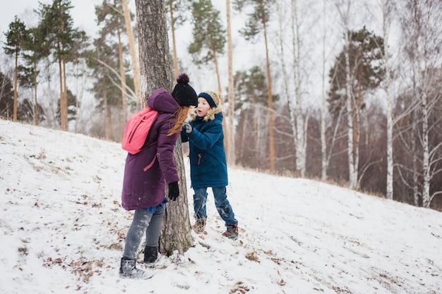 Het meisje bevindt zich dichtbij een boom met haar jongere broer, de wintergang in het bos of het park Premium Foto