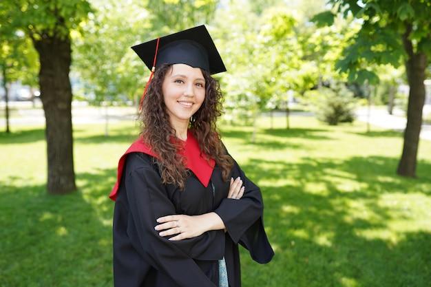 Het meisje bevindt zich in groen park dichtbij universiteit Premium Foto