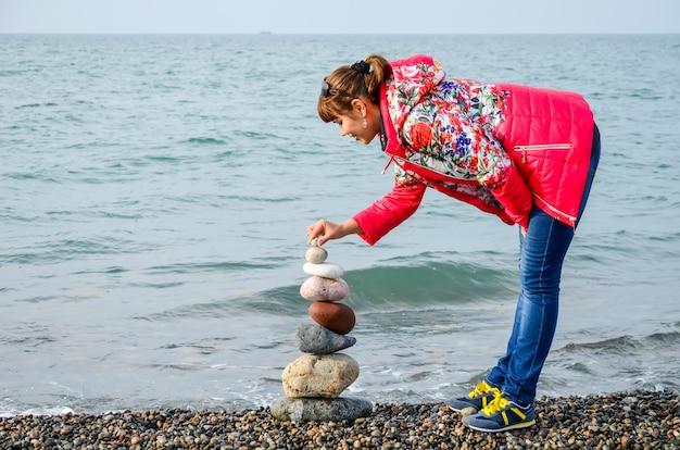 Het meisje bouwt een piramide van gekleurde stenen op de zwarte zee in batumi, georgië. Premium Foto
