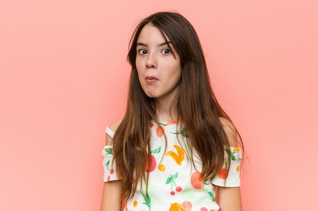 Het meisje dat de zomer draagt kleedt zich tegen een rode muur schouders op en verwarde open ogen. Premium Foto
