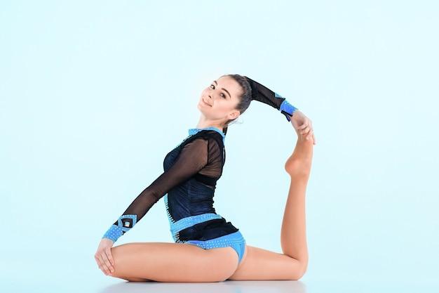 Het meisje dat gymnastiekdans doet op een blauwe muur Gratis Foto