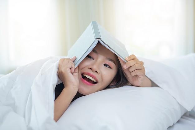 Het meisje dat in bed ligt dat aan muziek luistert en boeken leest. Gratis Foto