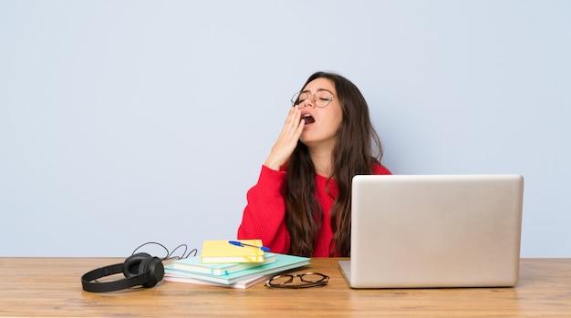 Het meisje die van de tienerstudent in een lijst bestuderen die en wijd open mond geeuwen behandelen met hand Premium Foto