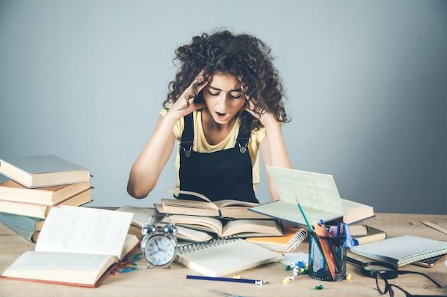 Het meisje dient haar met boeken op bureau in Premium Foto
