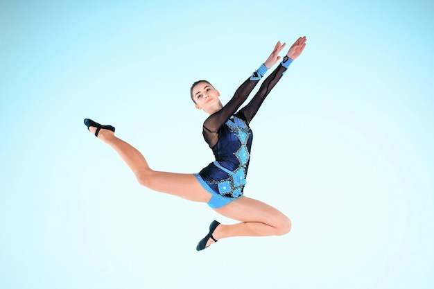 Het meisje doet gymnastiek dansen op een blauwe achtergrond Gratis Foto