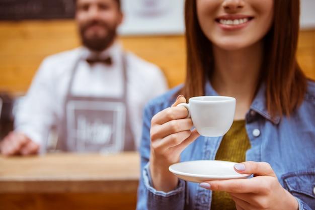 Het meisje drinkt koffie in een koffiewinkel en glimlacht. Premium Foto