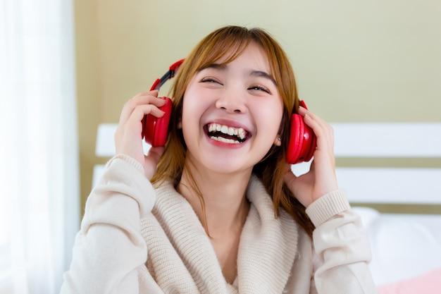 Het meisje droeg een koptelefoon en genoot van muziek op het bed Gratis Foto