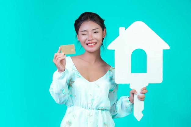 Het meisje droeg een wit shirt met lange mouwen en een bloemenpatroon, met een wit huissymbool en een gouden creditcard met een blauwe. Gratis Foto