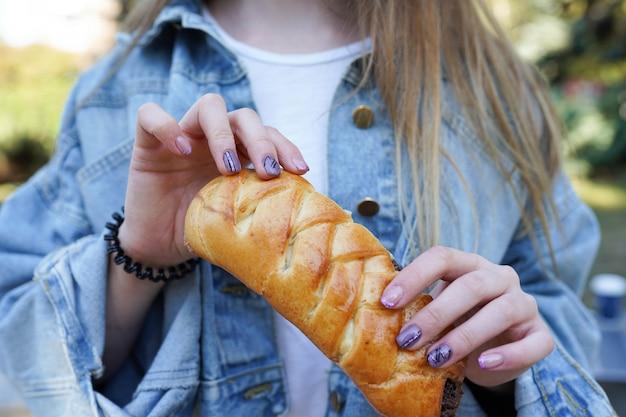 Het meisje eet broodje met chocolade op de straat Premium Foto