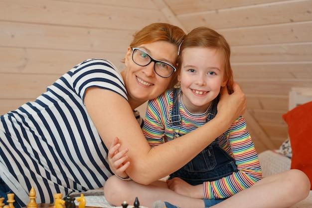 Het meisje en haar moeder glimlachen. portret van een dochter en een moeder Premium Foto