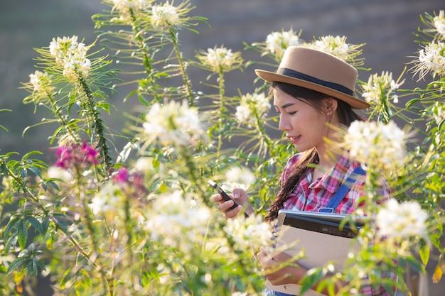 Het meisje fotografeert bloemen met een mobiele camera. Gratis Foto