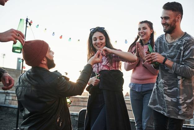Het meisje geeft haar pinkvinger. verklaring van liefde op het dak met vrienden Gratis Foto