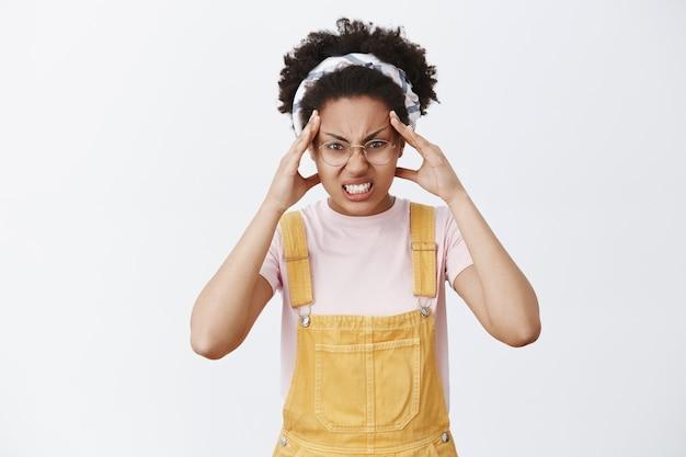 Het meisje gelooft dat ze objecten met kracht van geest kan verplaatsen. portret van grappig en boos schattig vrouwtje in tuinbroek, hoofdband en bril, fronsend en gebalde tanden met woede, vingers op voorhoofd houden Gratis Foto
